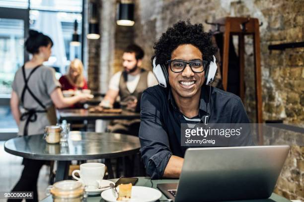 Young man with wearing glasses and headphones using laptop in cafe