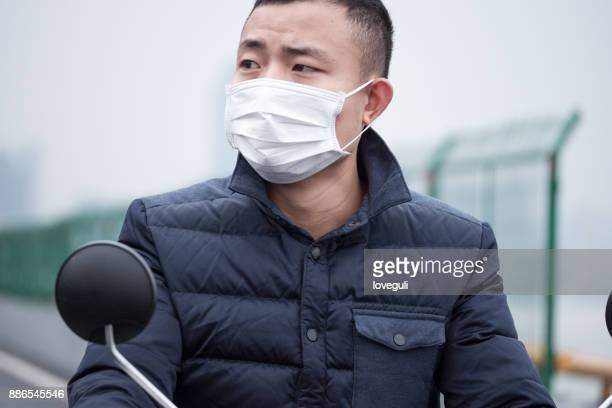 young man with white mask rides on motorcycle - chinese mask stock photos and pictures