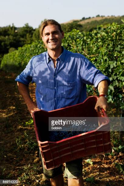 young man with wine grape. standing in field