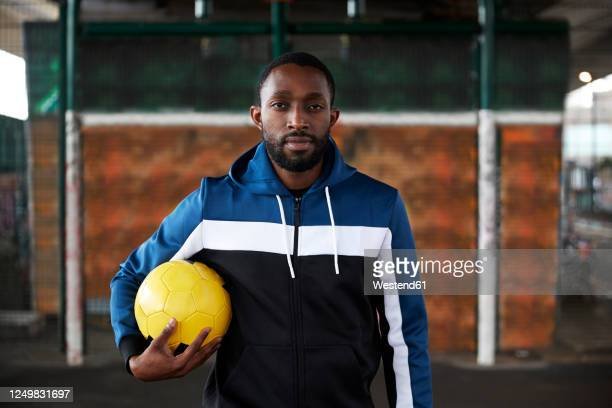 young man with yellow football - football player stock pictures, royalty-free photos & images