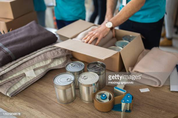 young man working at charitable foundation, packing donation box - food bank stock pictures, royalty-free photos & images