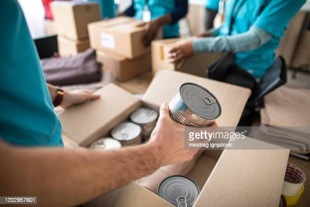 young man working at charitable foundation, packing donation box - charity and relief work stock pictures, royalty-free photos & images