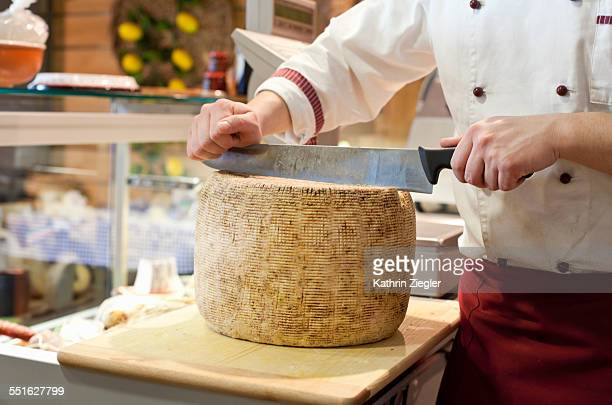 young man working at delicatessen, cutting cheese