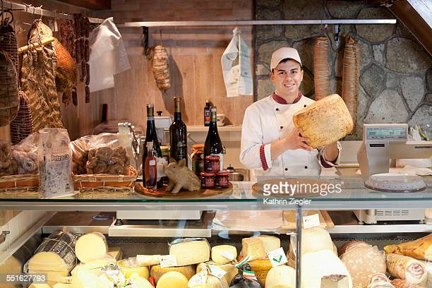 young man working at delicatessen, holding cheese - delicatessen stock pictures, royalty-free photos & images