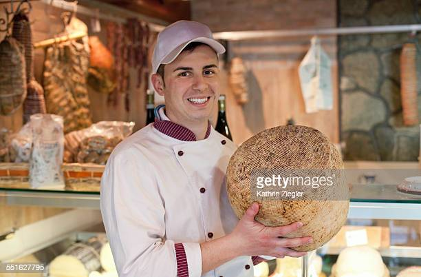 young man working at delicatessen, holding cheese