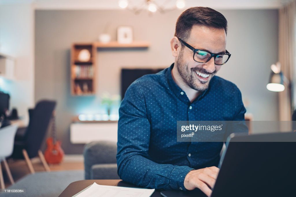 Young man working at home in the evening : Stock Photo