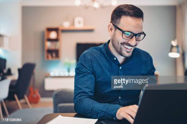 young man working at home in the evening - e mail stock pictures, royalty-free photos & images