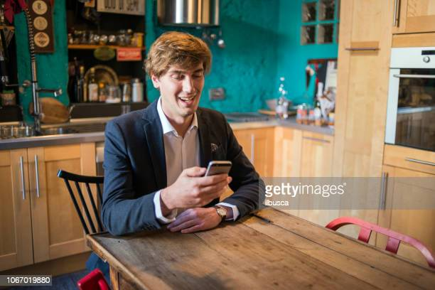 Young man working at home on smartphone