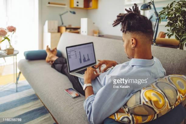 junger mann zu hause - finanzberuf stock-fotos und bilder