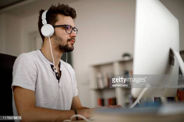 young man working at home - damircudic stock photos and pictures