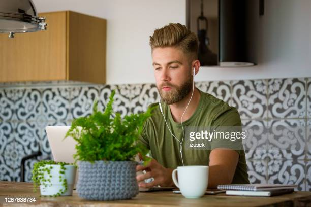 young man working at home - serious stock pictures, royalty-free photos & images
