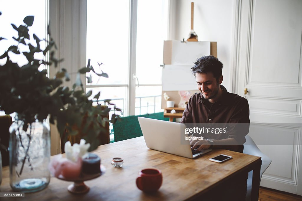 Young man working at home : Stock Photo