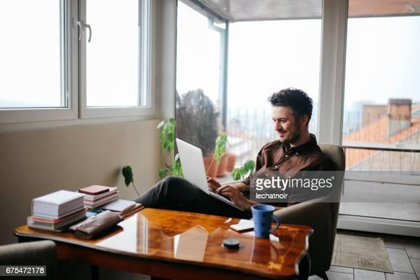 junger mann, arbeiten von zuhause  - laptop benutzen stock-fotos und bilder