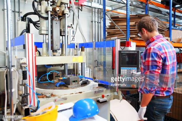 young man working at manufacturing factory - da vinci robot stock pictures, royalty-free photos & images