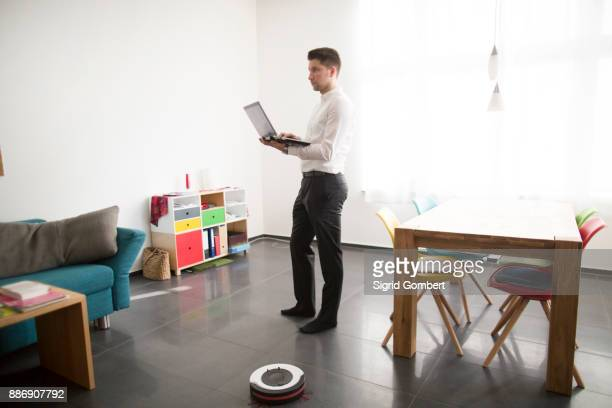 Young man working from home, standing while typing on laptop