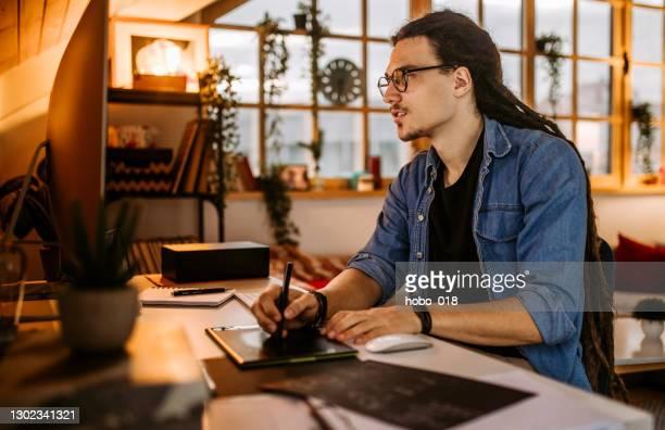 jovem trabalhando seu projeto em home office - trabalho de freelancer - fotografias e filmes do acervo
