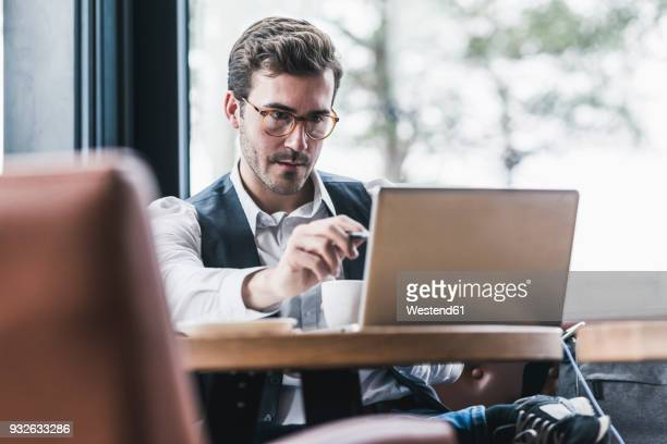 Young man working in a cafe using laptop and taking notes