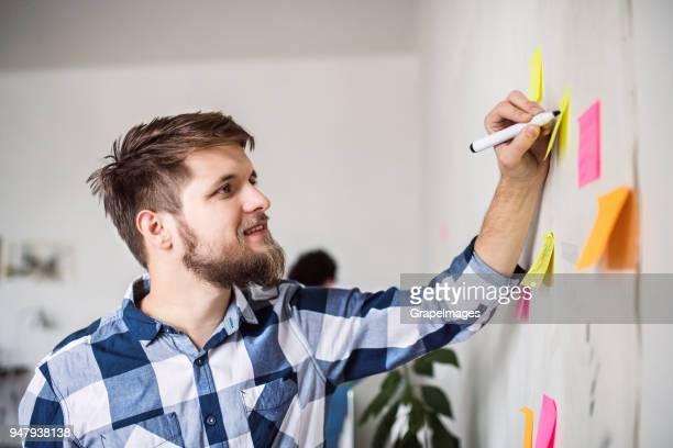 jonge man die werkt in een kantoor of een studio. - linkshandig stockfoto's en -beelden