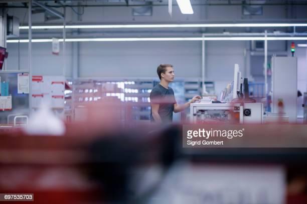 Young man working in books printing industry, Bremgarten, Hartheim am Rhein, Baden-Wuerttemberg, Germany