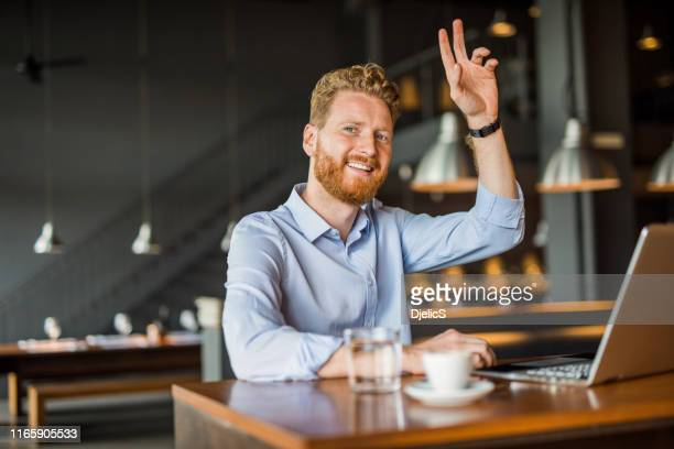 young man working in coffee shop and calling a waiter. - waving gesture stock pictures, royalty-free photos & images