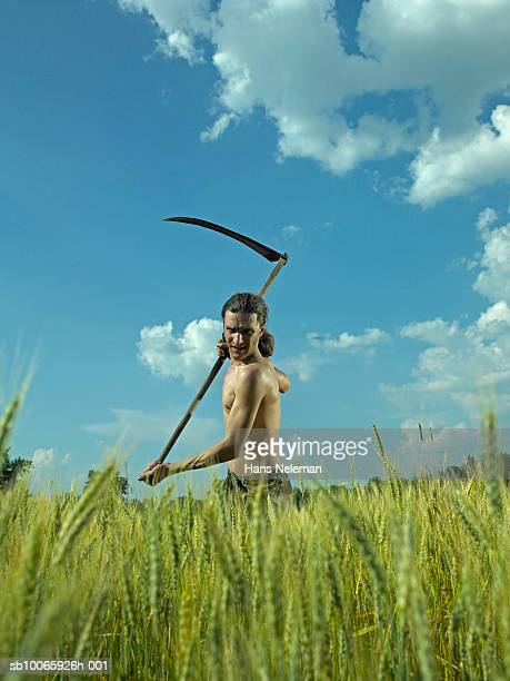 Young man working in field with scythe