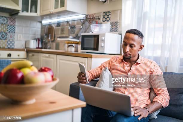 jonge mens die in zijn huisbureau werkt - latijns amerikaanse en hispanic etniciteiten stockfoto's en -beelden