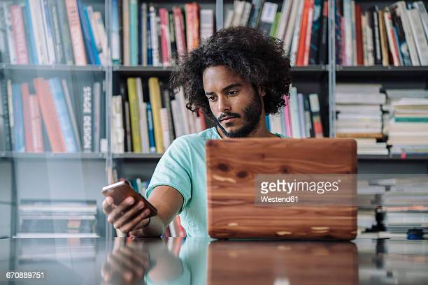 Young man working in library, using wooden laptop