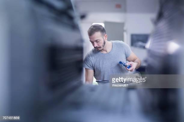 young man working in printing shop - variable schärfentiefe stock-fotos und bilder