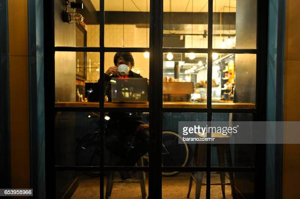 Young man working late in a coffee shop
