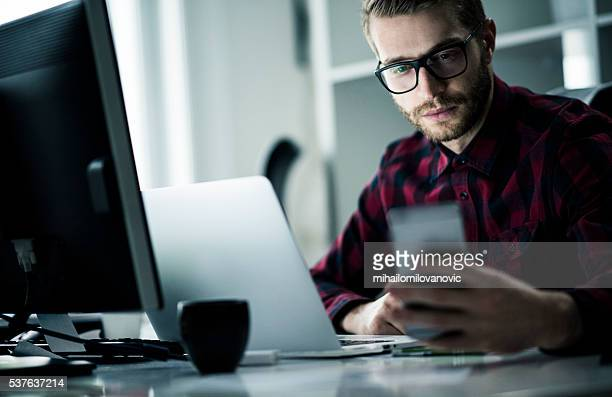 Hombre joven trabajando hasta tarde en su oficina