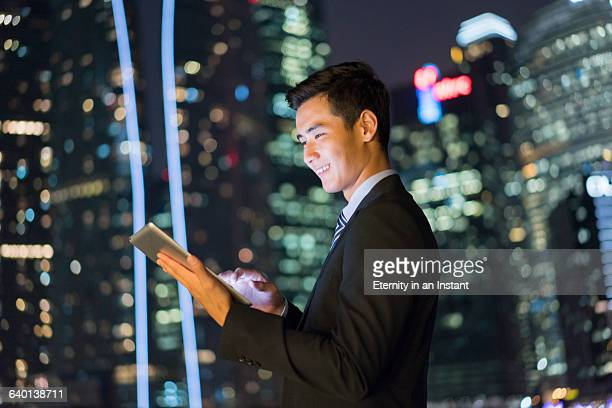 Young man working on a digital tablet at night