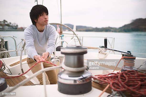 若い男性に取り組んでいる、ヨット - もがく ストックフォトと画像