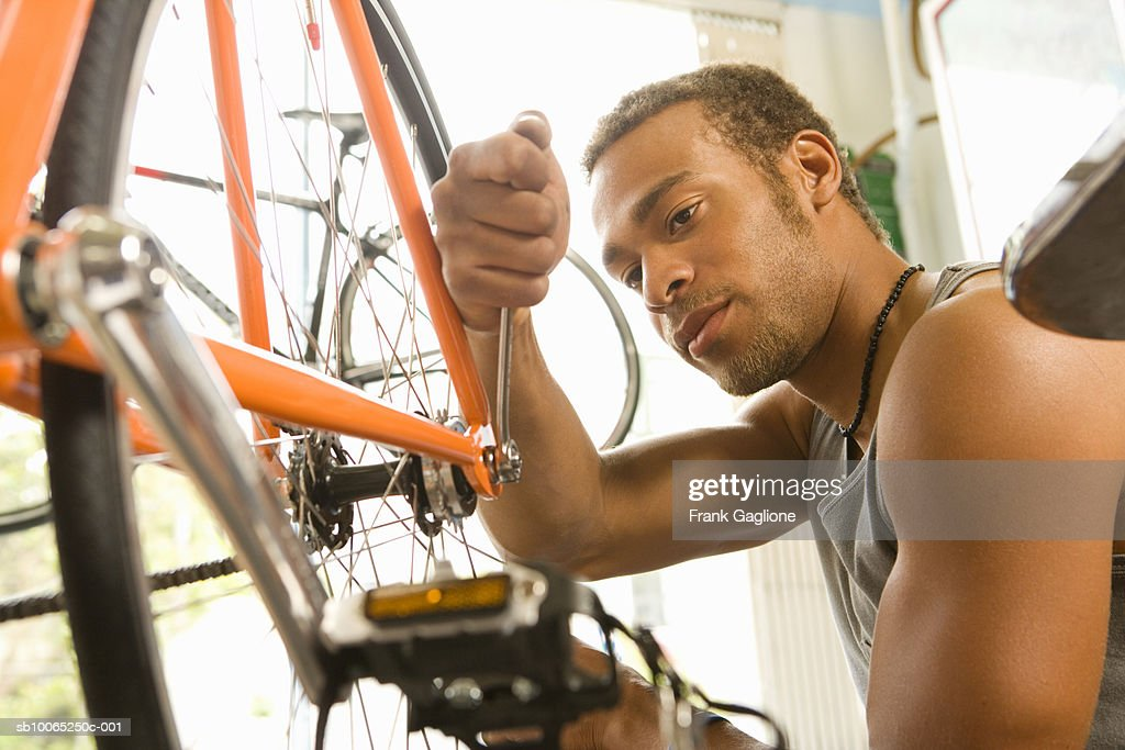 Young man working on bicycle indoors : Foto stock