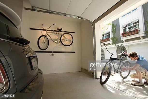 Young Man Working on Bike in Garage