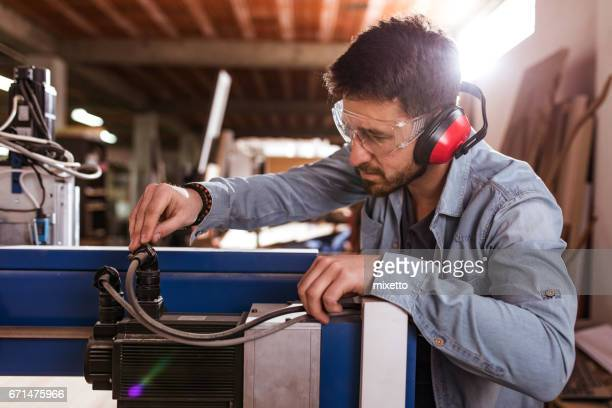 Young man working on cnc machine