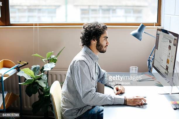 young man working on computer in studio - small office stock pictures, royalty-free photos & images