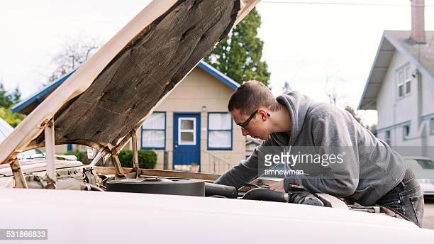 Junger Mann arbeitet auf seinem Auto
