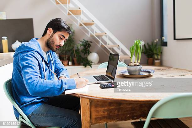 Young man working on his laptop at home.