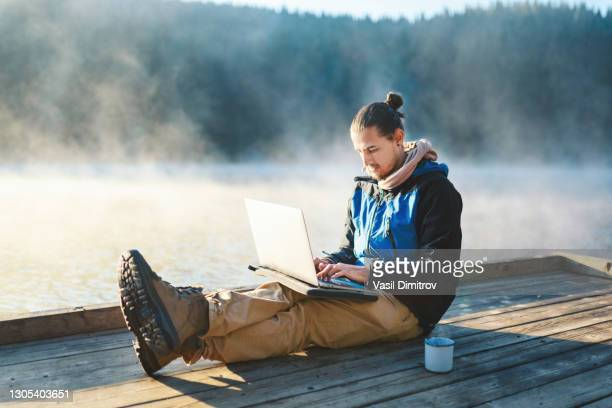 young man working on his laptop in the nature. leisure activities / remote working concept. - nomadic people stock pictures, royalty-free photos & images