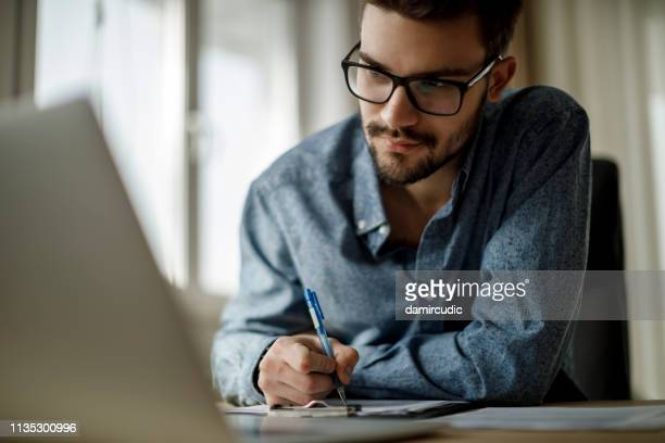 young man working on laptop and taking notes - studiare foto e immagini stock