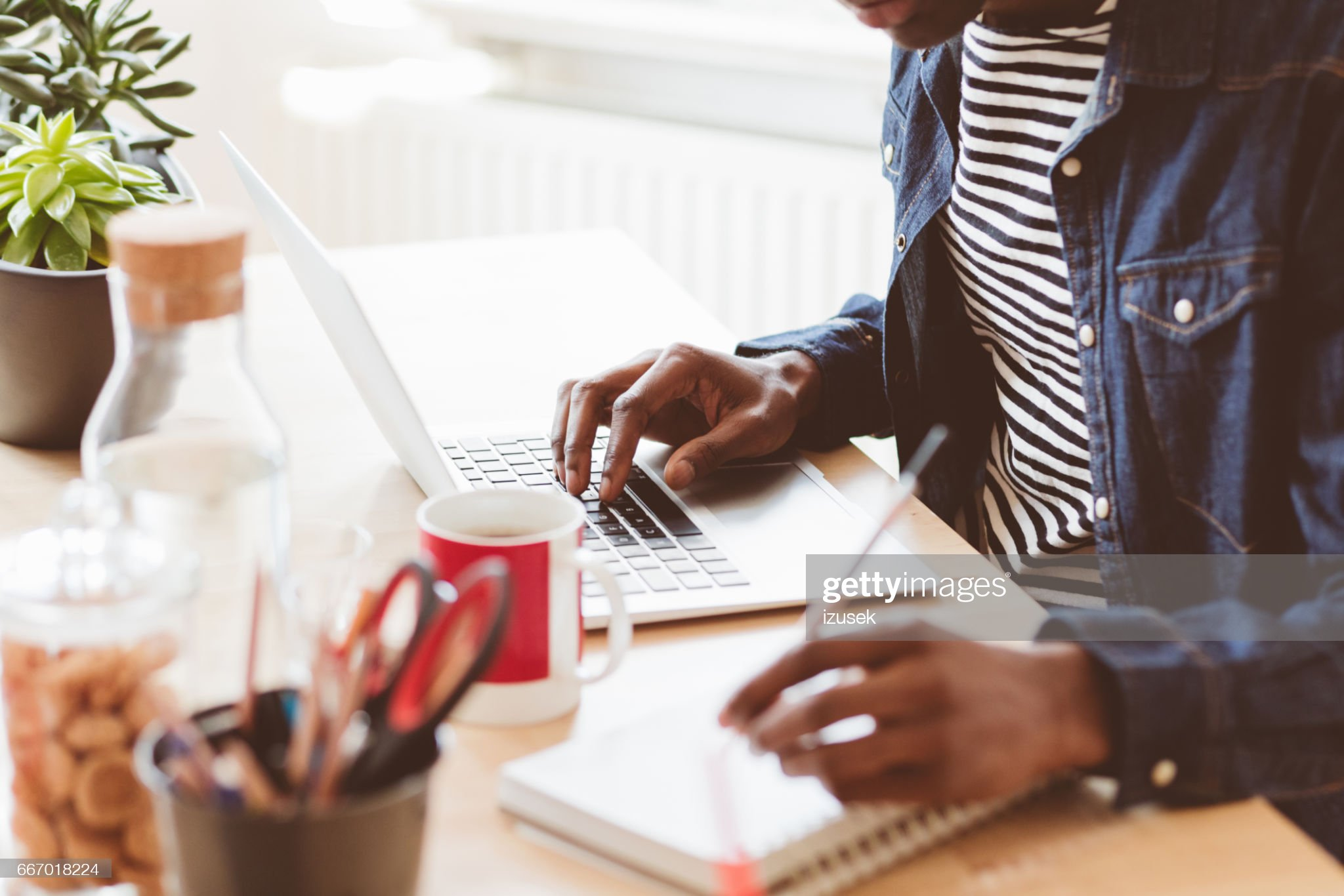Young man working on laptop and taking notes : Stock Photo