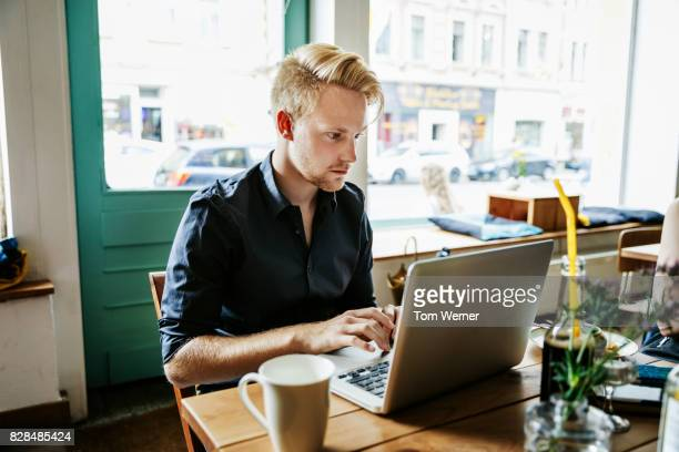 young man working on laptop in cafe - digital native stock pictures, royalty-free photos & images
