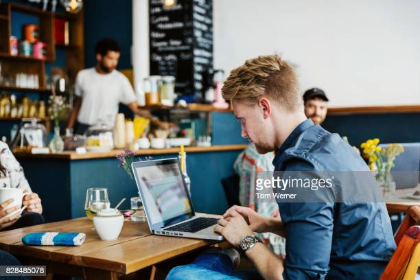 young man working on laptop in colourful coffee shop - digital native stock pictures, royalty-free photos & images
