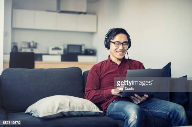若い男はヘッドフォンを身に着けている家でノート パソコンでの作業