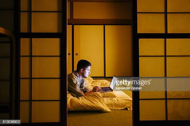 Young man working on laptop lying on the floor in traditional Japanese ryokan