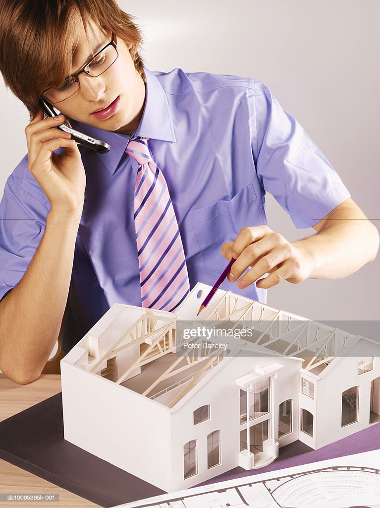 Young man working on model house, using mobile phone : Foto stock