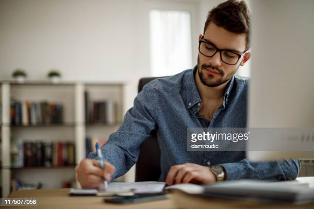 young man working - writing stock pictures, royalty-free photos & images