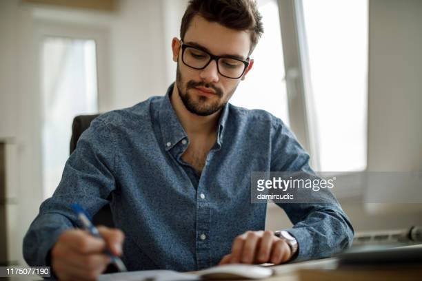 young man working - damircudic stock photos and pictures