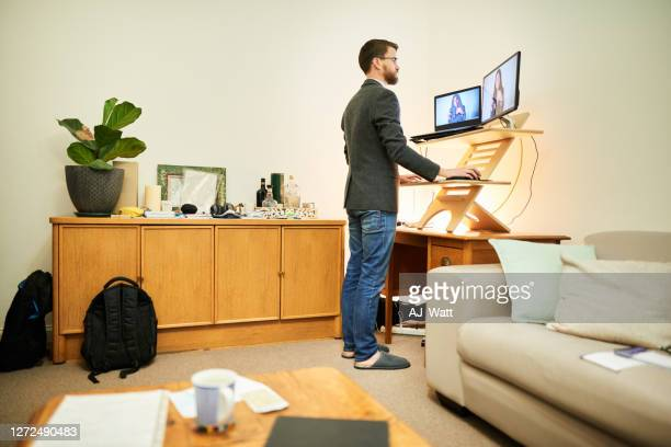 young man working remotely at a standing desk in his living room - standing stock pictures, royalty-free photos & images