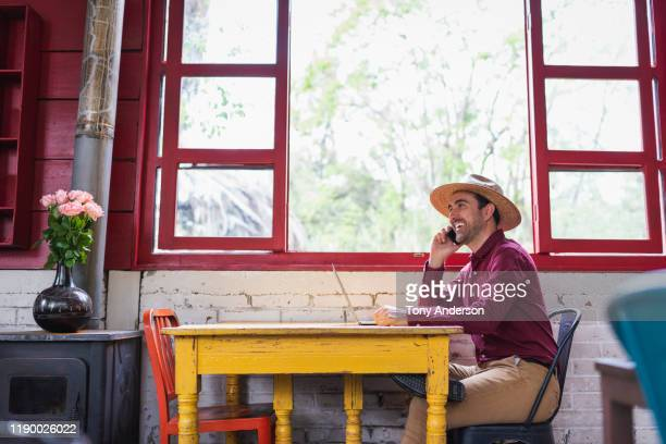 young man working with laptop and phone in coffee shop - mexico stock pictures, royalty-free photos & images